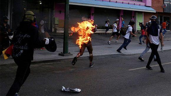 Un hombre al que prendieron fuego camina envuelto en llamas en Venezuela, durante las protestas de la oposición contra el presidente del país, Nicolas Maduro, el 20 de mayo de 2017. Foto: Marco Bello/ Reuters.